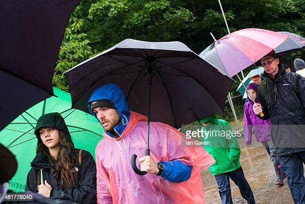 Festival goers shelter from the rain at the WOMAD Festival July 24 2015 in Malmesbury England
