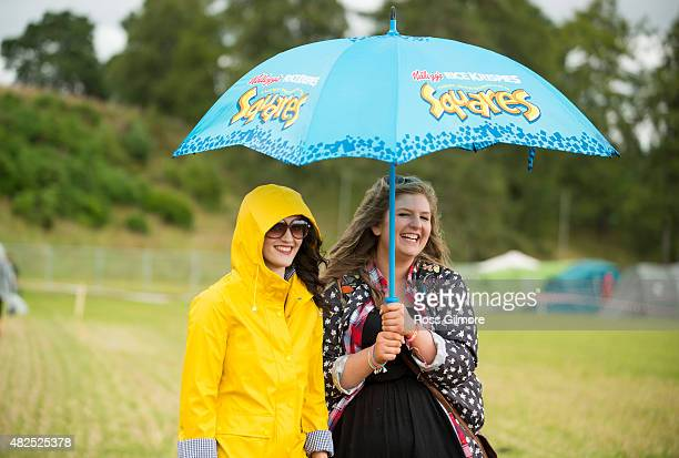 Festival goers shelter under an umbrella on day one of the Aviemore Stopover festival on July 31 2015 in Aviemore Scotland