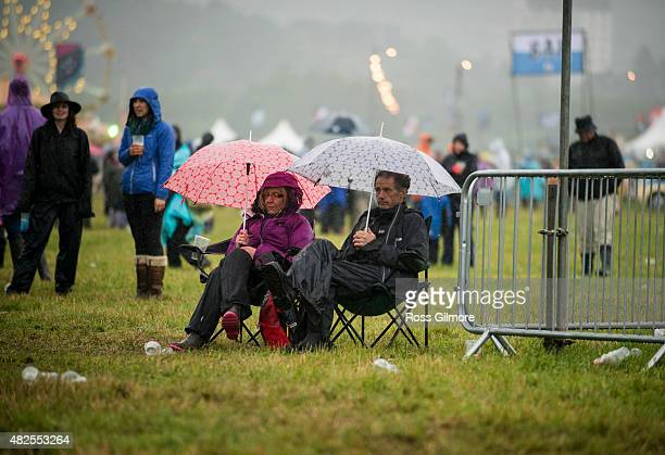 Festival goers sit on camp chairs in the rain at the Aviemore Stopover festival on July 31 2015 in Aviemore Scotland
