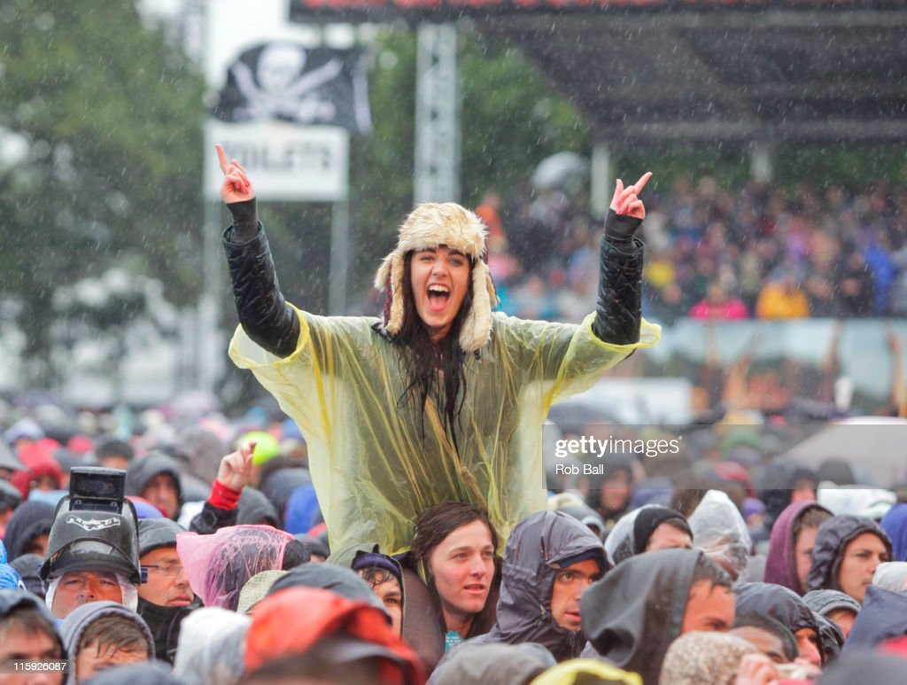 Festival goers stand in the rain during day three of the Isle of Wight Festival at Seaclose Park on June 12, 2011 in Newport, Isle of Wight.