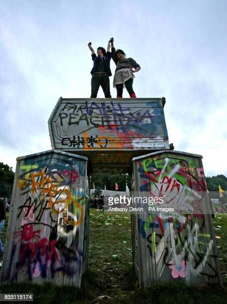 Festival goers stand on an installation by the artist Banksy to celebrate the mid summer solstice at the stone circle at Worthy Farm in Pilton...