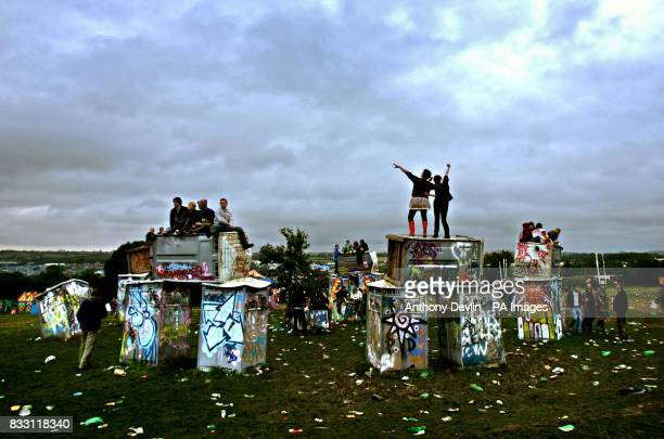 Festival goers stand on an installation by the artist Banksy to celebrate the mid summer solstice at the stone circle at the Glastonbury Festival at...