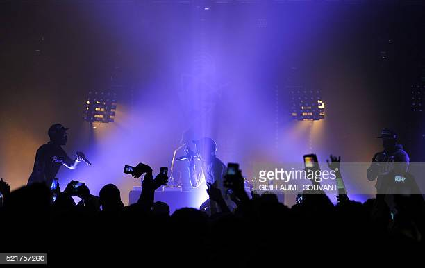 Festival goers take pictures with their smartphones as the hiphop french band MHD performs at the 40th edition of 'Le Printemps de Bourges' rock and...
