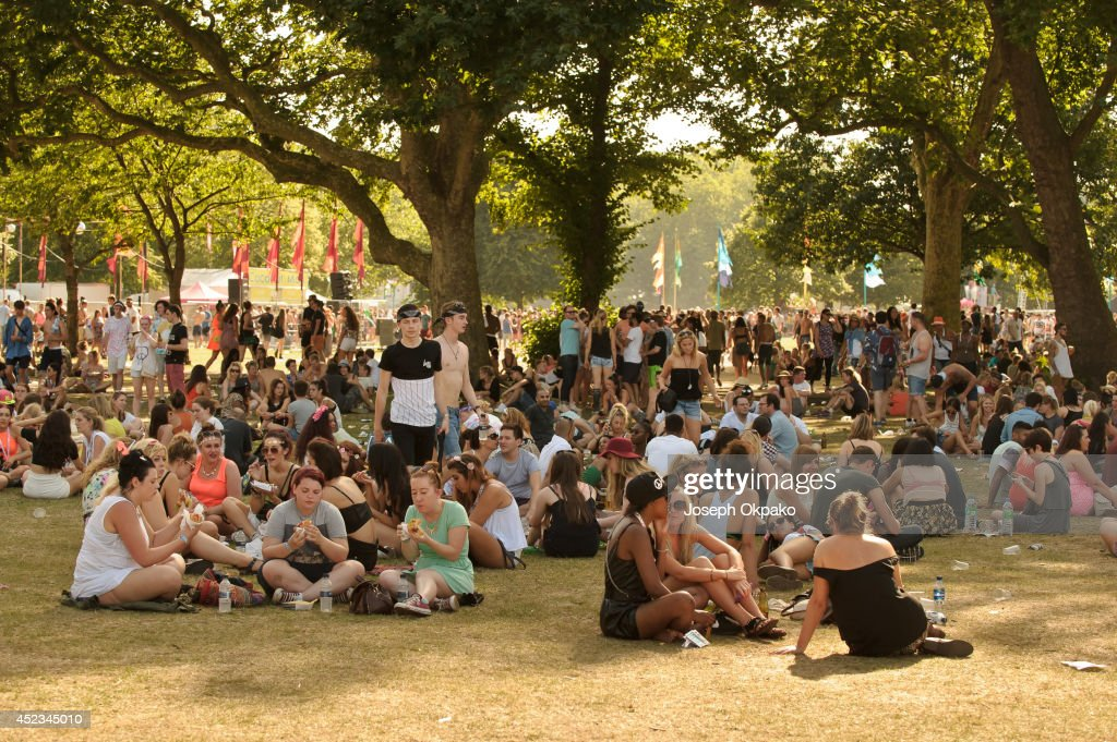 Festival goers take shelter under the trees at Lovebox 2014 at Victoria Park on July 18 2014 in London United Kingdom