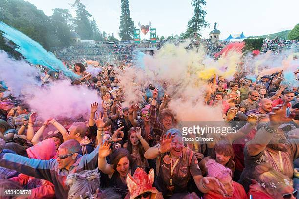 Festival goers throw colored powder at the main stage at Belladrum Tartan Hearts Festival at on August 9 2014 in Inverness United Kingdom
