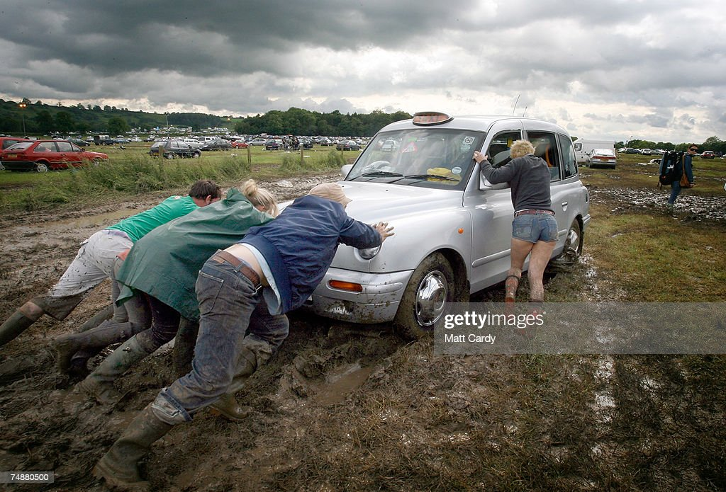 Festival goers try to push a taxi cab that has got stuck in the mud at the Glastonbury Festival site at Worthy Farm, Pilton near Glastonbury on June 25 2007, in Somerset, England. The event started by dairy farmer Michael Eavis in 1970 is now Europe's largest music festival.