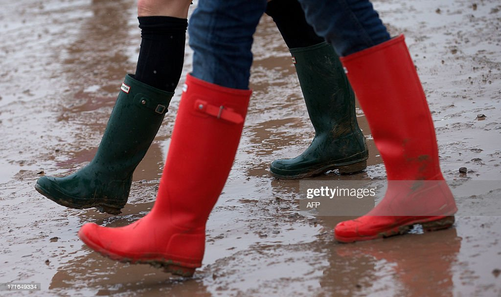 Festival goers walk around the site in rain boots on the second day of the Glastonbury Festival of Contemporary Performing Arts near Glastonbury, southwest England, on June 27, 2013. The festival attracts 170,000 party-goers to the dairy farm in Somerset, and this year's tickets sold out within two hours of going on sale. The Rolling Stones will perform at the festival for the first time, headlining on Saturday night.