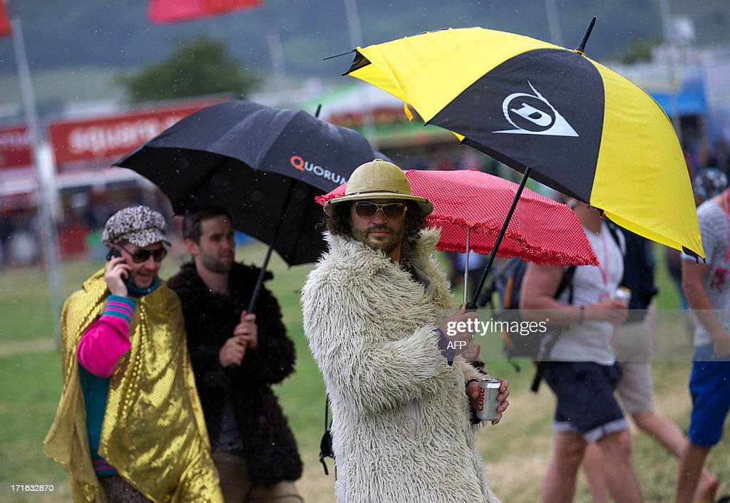 Festival goers walk around the site on the second day of the Glastonbury Festival of Contemporary Performing Arts near Glastonbury, southwest England, on June 27, 2013. The festival attracts 170,000 party-goers to the dairy farm in Somerset, and this year's tickets sold out within two hours of going on sale. The Rolling Stones will perform at the festival for the first time, headlining on Saturday night. AFP PHOTO/ANDREW COWIE