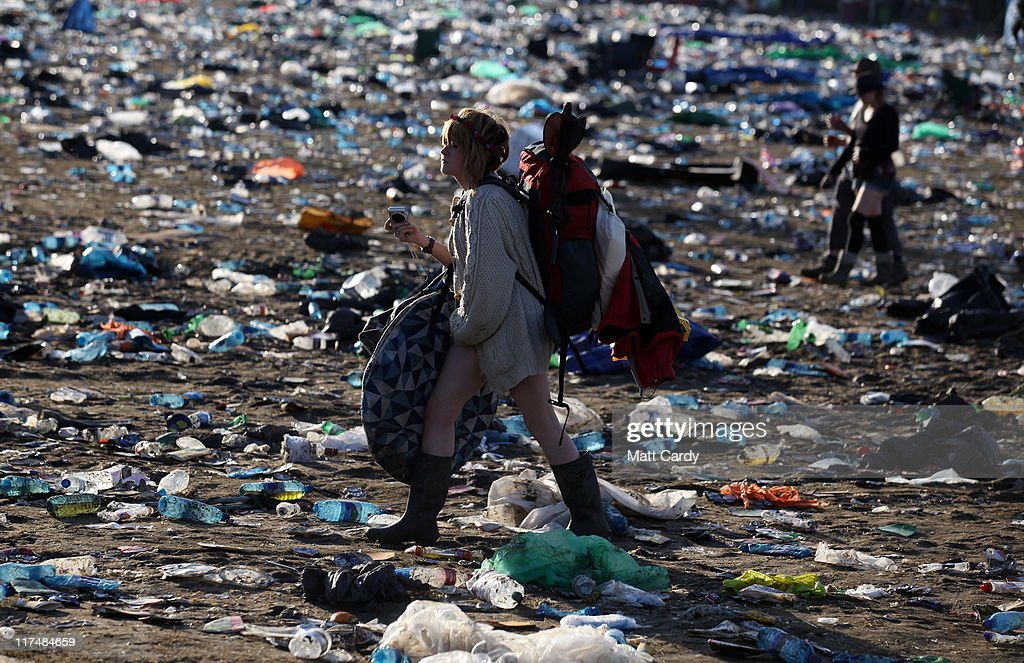 Festival goers walk through rubbish left in the main arena in front of the Pyramid Stage as they begin to leave the Glastonbury Festival site on June 27, 2011 at Worthy Farm, Pilton. As the 170,000 plus music fans began to leave this morning the clean up of the 1000s of tonnes of rubbish left by them begins. The festival, which started in 1970 when several hundred hippies paid 1 GBP to watch Marc Bolan, has grown into Europe's largest music festival attracting more than 175,000 people over five days.
