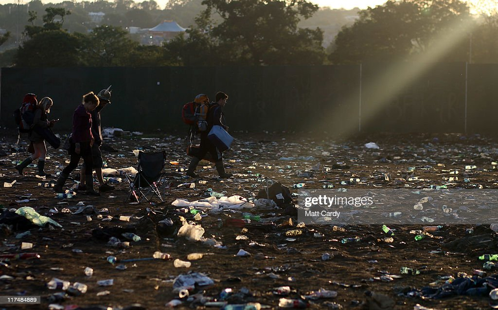Festival goers walk through rubbish left in the main arena in front of the Other Stage as they begin to leave the Glastonbury Festival site on June 27, 2011 at Worthy Farm, Pilton. As the 140,000 plus music fans began to leave this morning the clean up of the 1000s of tonnes of rubbish left by them begins. The festival, which started in 1970 when several hundred hippies paid 1 GBP to watch Marc Bolan, has grown into Europe's largest music festival attracting more than 175,000 people over five days.