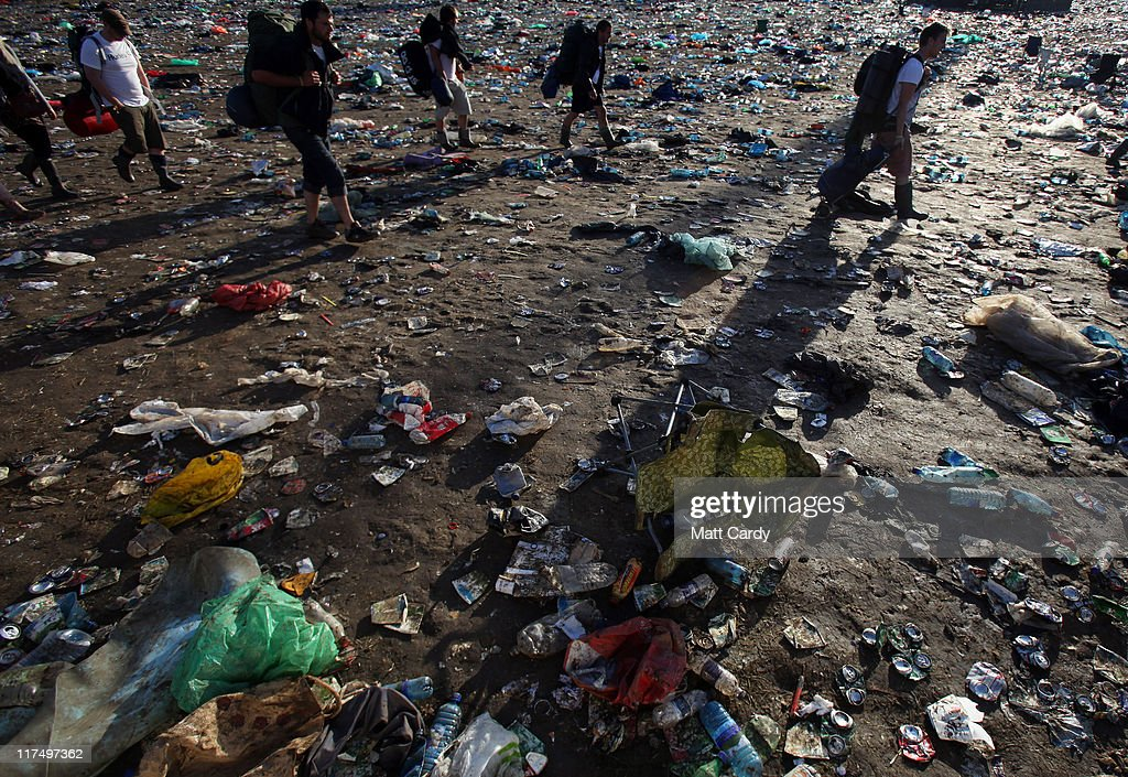 Festival goers walk through rubbish left in the main arena in front of the Pyramid Stage as they begin to leave the Glastonbury Festival site at Worthy Farm, Pilton on June 27, 2011. As the 140,000 plus music fans began to leave this morning the clean up of the 1000s of tonnes of rubbish left by them begins. The festival, which started in 1970 when several hundred hippies paid 1 GBP to watch Marc Bolan, has grown into Europe's largest music festival attracting more than 175,000 people over five days.