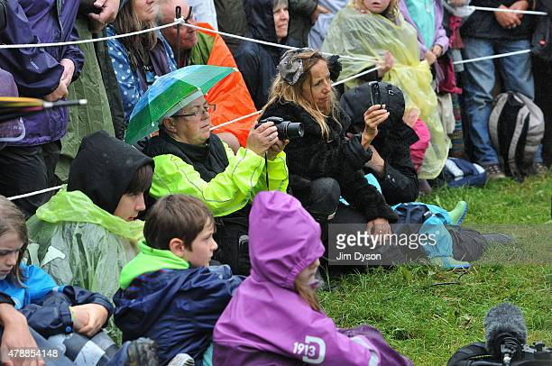 Festival goers watch the Dalai Lama give a talk in the rain during the third day of Glastonbury Festival at Worthy Farm Pilton on June 28 2015 in...