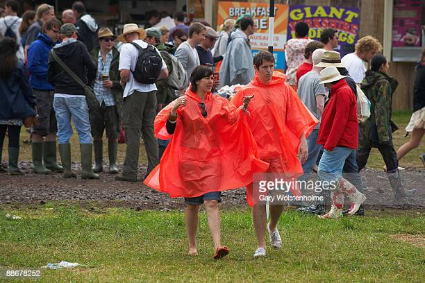 Festival goers wearing ponchos in the rain on the first day of Glastonbury Festival at Worthy Farm on June 25 2009 in Glastonbury Somerset England