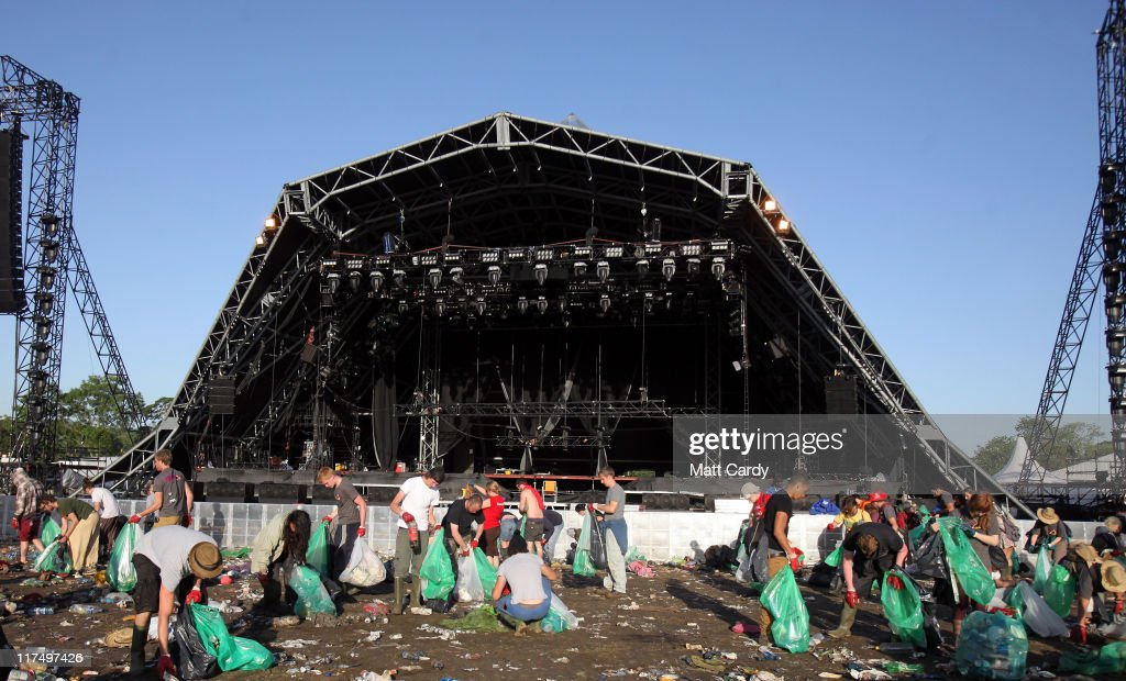 Festival litter-pickers begin to clear the rubbish left in the main arena in front of the Pyramid Stage as festival goers begin to leave the Glastonbury Festival site at Worthy Farm, Pilton on June 27, 2011. As the 140,000 plus music fans began to leave this morning the clean up of the 1000s of tonnes of rubbish left by them begins. The festival, which started in 1970 when several hundred hippies paid 1 GBP to watch Marc Bolan, has grown into Europe's largest music festival attracting more than 175,000 people over five days.