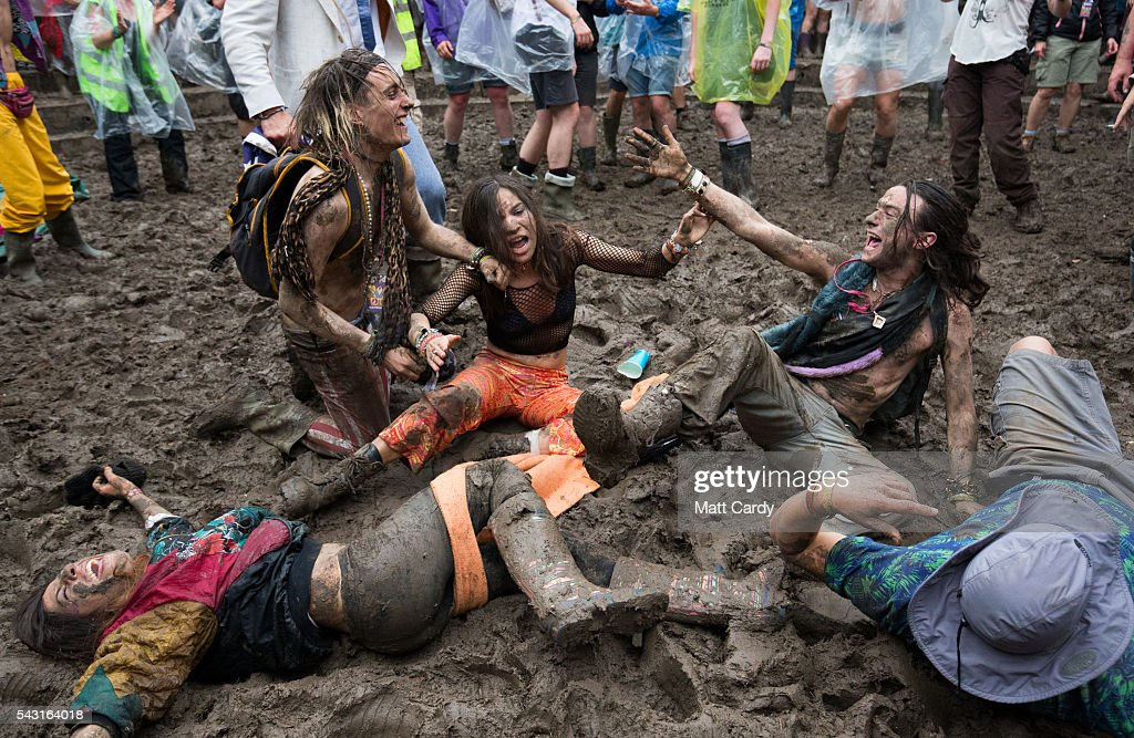Festival revellers roll in the mud as they prepare to take part in a tomato fight at the Glastonbury Festival 2016 at Worthy Farm, Pilton on June 25, 2016 near Glastonbury, England. The Festival, which Michael Eavis started in 1970 when several hundred hippies paid just £1, now attracts more than 175,000 people.