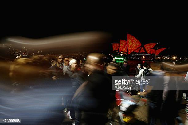 Festival visitors are seen as the 'Lighting The Sails' installation illuminates the Sydney Opera House as part of the Vivid Sydney Festival on May 24...