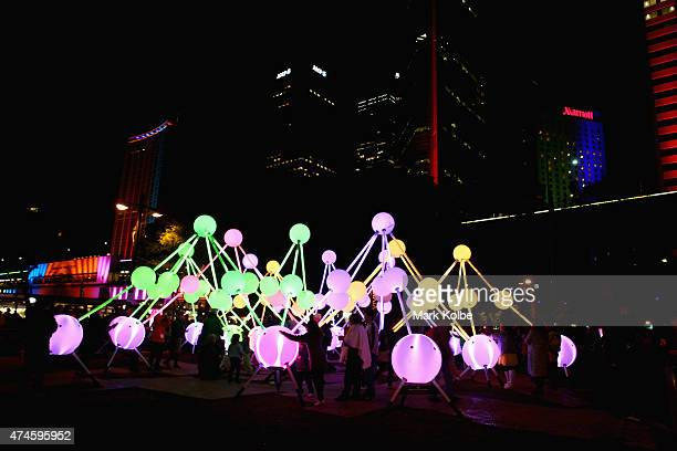 Festival visitors interact with the 'Affinity' installation illuminated as part of the Vivid Sydney Festival on May 24 2015 in Sydney Australia Vivid...