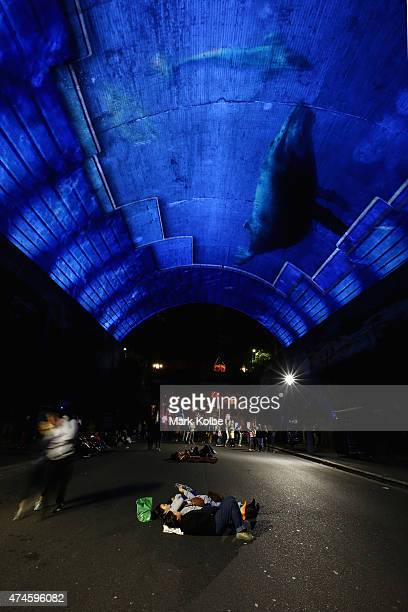 Festival visitors lie on the road as they watch the 'Life Story' installation projected on the vaulted roof of the Argyle Cut as part of the Vivid...