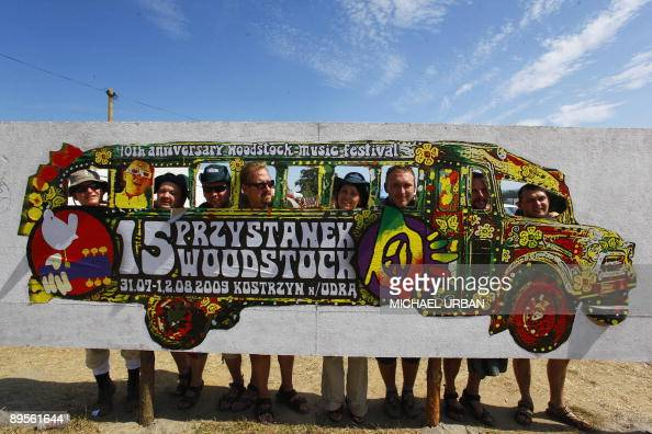 Festival visitors pose for a photos with a giant logo during the socalled 'Woodstock Stop' openair festival in the Polish town of Kuestrin on August...