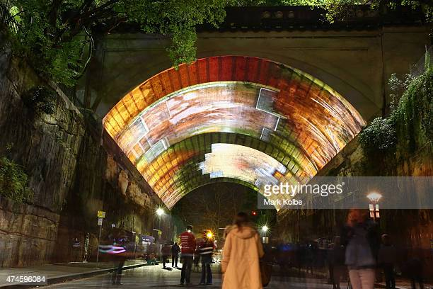 Festival visitors watch the 'Life Story' installation projected on the vaulted roof of the Argyle Cut as part of the Vivid Sydney Festival on May 24...