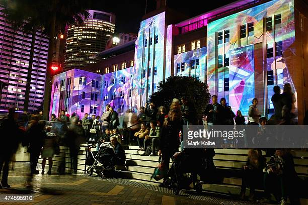 Festival visitors watch the 'Lighting The Sails' on the Sydney Opera House from in front of the 'Mechanised Colour Assemblage' installation...