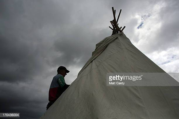 A festival worker helps erect one of the several hundred tipi tents that will be eventually available for hire at the Glastonbury Festival of...