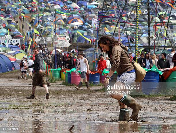 A festivalgoer carefully walks through a puddle during the opening day of the Glastonbury festival near Glastonbury Somerset on June 23 2011 Veteran...