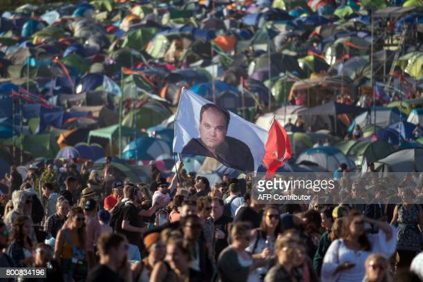 A festivalgoer carries a flag bearing the image of actor Shaun Williamson who is best known for playing the character Barry Evans in the soap opera...