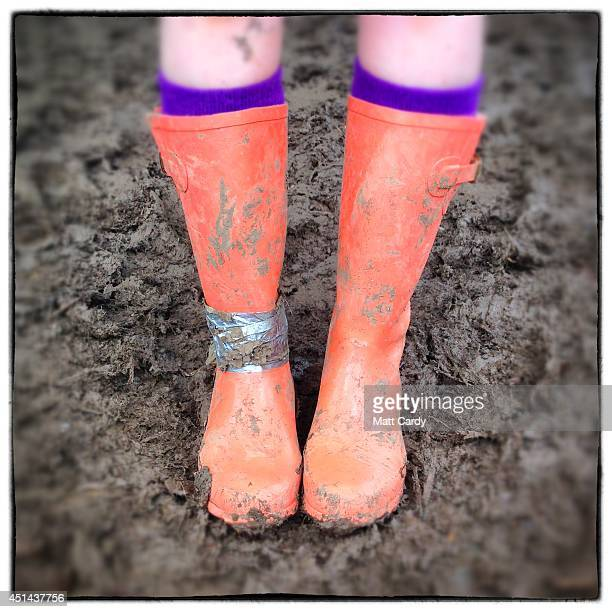 Festivalgoer Catherine Ryder poses in the mud with her wellies bought from Primark for £8 at the Glastonbury Festival site on June 29 2014 in...
