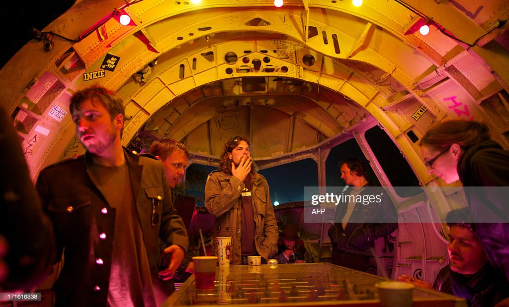 Festivalgoer drink in a bar made out of a cockpit of a aeroplane on the first night of the Glastonbury Festival of Contemporary Performing Arts near Glastonbury, southwest England late on June 26, 2013. The festival attracts 170,000 party-goers to the dairy farm in Somerset, and this year's tickets sold out within two hours of going on sale. The Rolling Stones will perform at the festival for the first time, headlining on Saturday night.