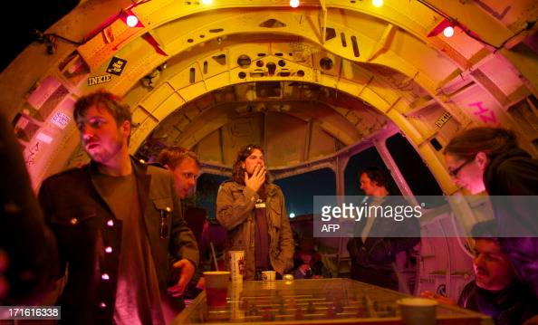 Festivalgoer drink in a bar made out of a cockpit of a aeroplane on the first night of the Glastonbury Festival of Contemporary Performing Arts near...