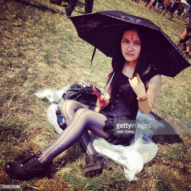 A festivalgoer from China takes shade from the hot sun under an umbrella at the 2014 Wacken Open Air heavy metal music festival on on July 31 2014 in...