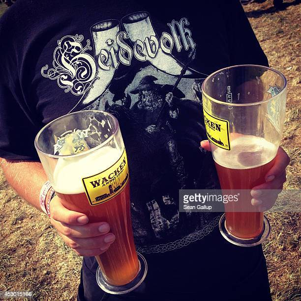 A festivalgoer holds two glasses of beer at the 2014 Wacken Open Air heavy metal music festival on on August 1 2014 in Wacken Germany Wacken is a...