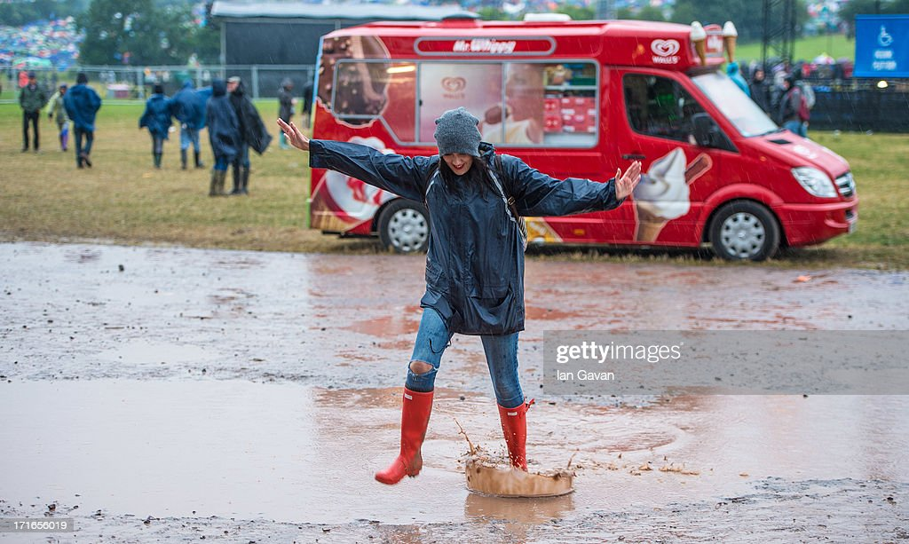 A festival-goer jumps through a puddle as rain falls during day 1 of the 2013 Glastonbury Festival at Worthy Farm on June 27, 2013 in Glastonbury, England.