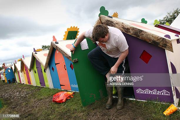 A festivalgoer puts on his wellies outside his sleeping pod after waking up during the Glastonbury festival near Glastonbury Somerset on June 25 2011...
