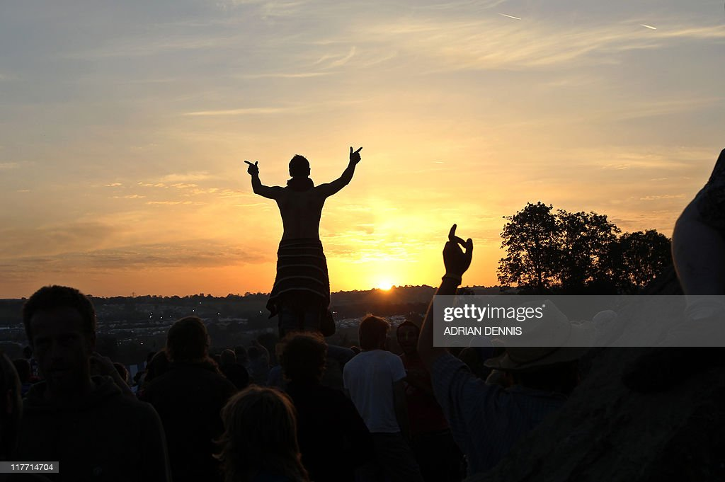 A festival-goer reacts while the sun rises over the Stone Circle after the final day of the Glastonbury festival near Glastonbury, Somerset, on June 27, 2011. US soul diva Beyonce on Sunday brought Britain's Glastonbury festival to a flamboyant finale with a greatest hits and covers set before of 100,000 sun-baked revellers. Despite a wet start to festivities on Thursday and Friday, the weather gods smiled on the 170,000 ticket holders with unbroken sunshine greeting artists performing at the farm in Somerset, south west England, on Saturday and Sunday. AFP PHOTO / Adrian Dennis