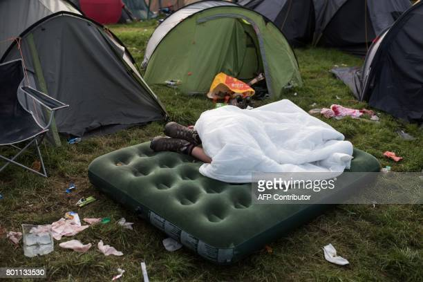 TOPSHOT A festivalgoer sleeps outside their tent at the end of the Glastonbury Festival of Music and Performing Arts on Worthy Farm near the village...