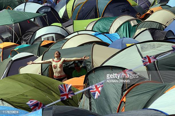 A festivalgoer stands amongst the tents and stretches out in the sun after having her body painted at the Glastonbury festival near Glastonbury...