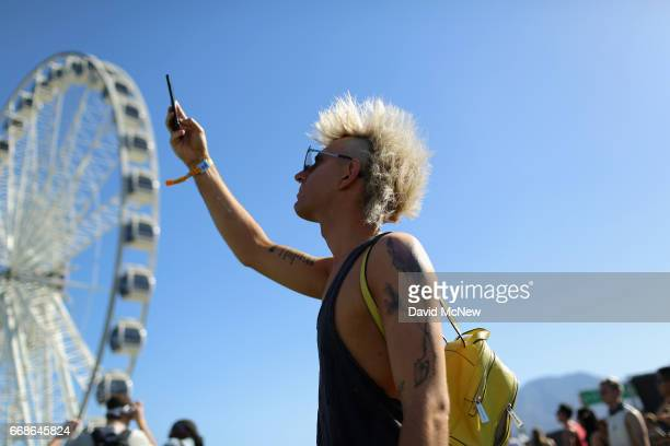 Festivalgoer takes a photo in front of the ferris wheel during day 1 of the Coachella Valley Music And Arts Festival at the Empire Polo Club on April...