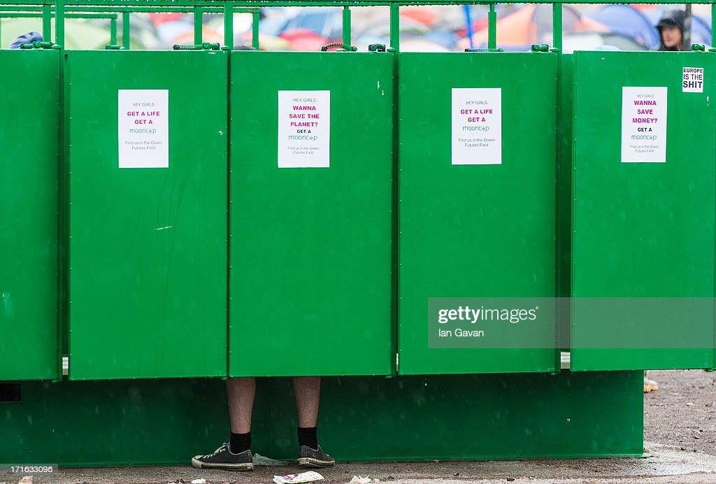 A festival-goer uses a toilet as rain falls during day 1 of the 2013 Glastonbury Festival at Worthy Farm on June 27, 2013 in Glastonbury, England.