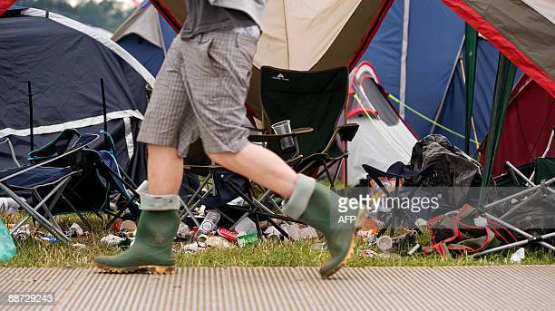 A festivalgoer walks past a deserted tent on the final evening of the annual Glastonbury festival near Glastonbury Somerset on June 28 2009 Running...