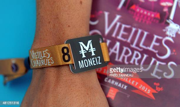 A festivalgoer wears a bracelet with the electronic payment system Moneiz during the Vieilles Charrues music festival in CarhaixPlouguer western of...