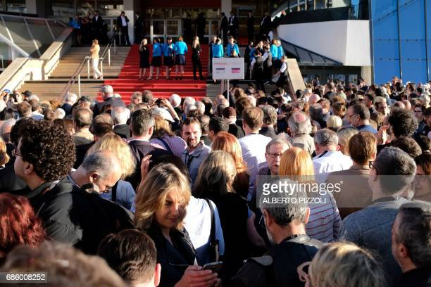 Festivalgoers and members of the media wait outside the main entrance of the Festival's Palace on May 20 2017 after it was evacuated over a...