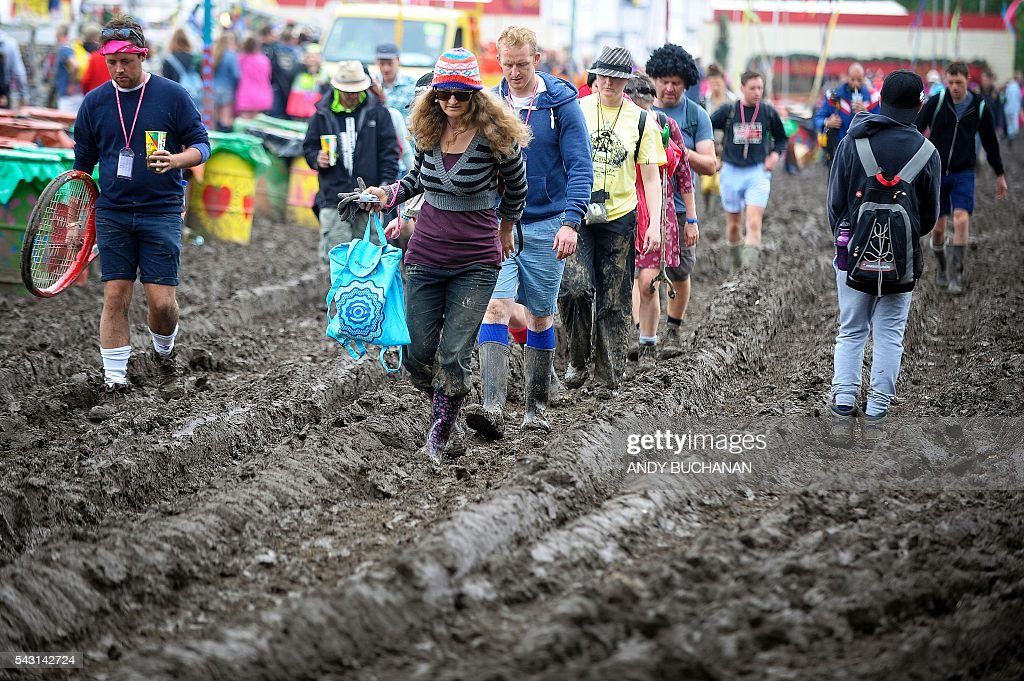 Festival-goers brave the muddy under-foot conditions on day five of the Glastonbury Festival of Music and Performing Arts on Worthy Farm near the village of Pilton in Somerset, South West England on June 26, 2016. / AFP / Andy Buchanan