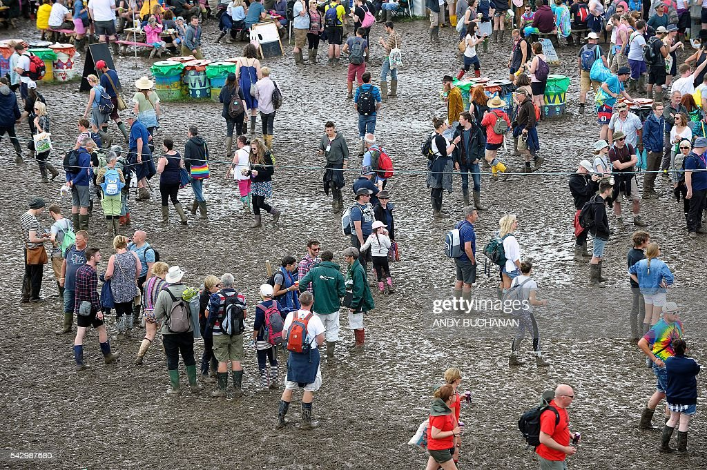 Festival-goers brave the muddy under-foot conditions on day four of the Glastonbury Festival of Music and Performing Arts on Worthy Farm near the village of Pilton in Somerset, South West England on June 25, 2016. / AFP / Andy Buchanan