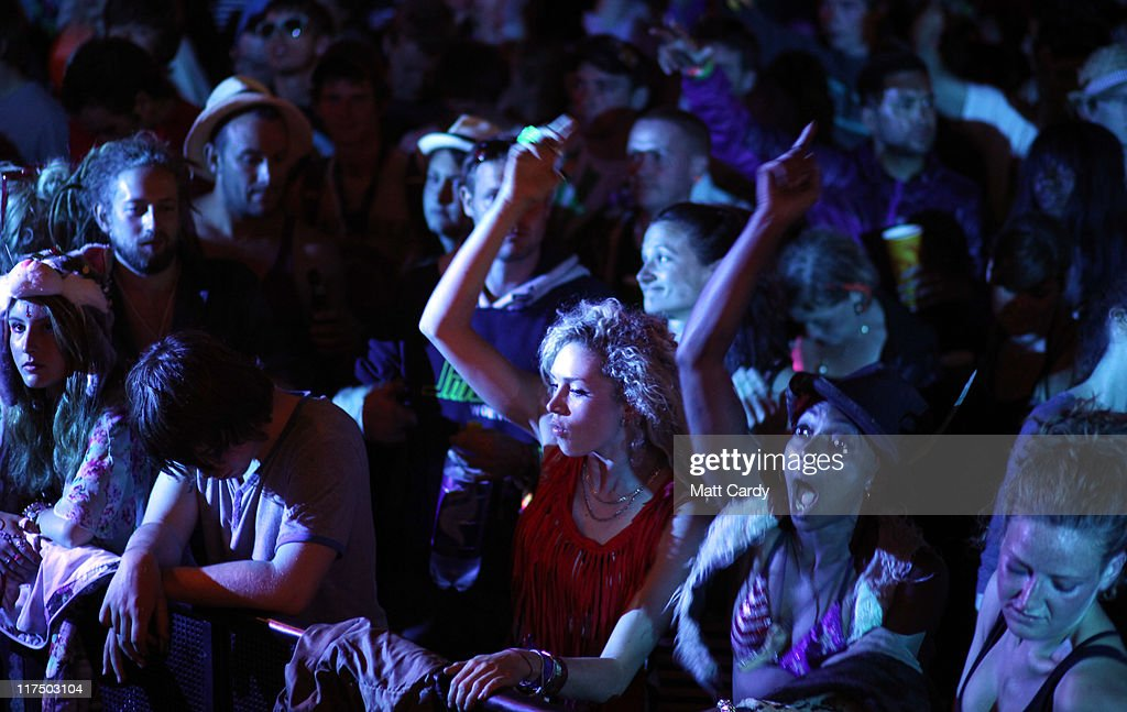 Festival-goers dance in the late night after hours Shangri-La area at the Glastonbury Festival site at Worthy Farm, Pilton on June 27, 2011. This year's festival featured headline acts U2, Coldplay and Beyonce. The festival, which started in 1970 when several hundred hippies paid 1 GBP to watch Marc Bolan, has grown into Europe's largest music festival attracting more than 175,000 people over five days.