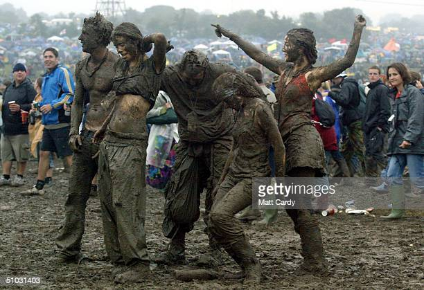 Festivalgoers dance in the mud in front of the Pyramid stage at Worthy Farm Pilton Somerset at the 2004 Glastonbury Festival 26 June 2004 The...