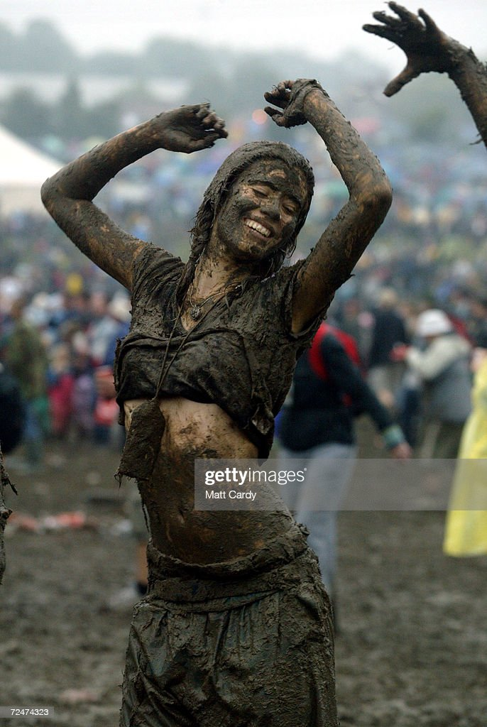 Festival-goers dance in the mud in front of the Pyramid stage at Worthy Farm, Pilton, Somerset, at the 2004 Glastonbury Festival, 26 June 2004. The festival spans over 3 days and runs until June 27.