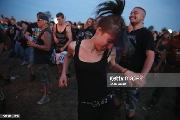Festivalgoers dance to a band at a minor stage at the 2014 Wacken Open Air heavy metal music festival on the eve of the first official concerts on...