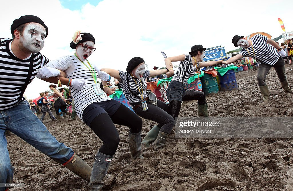 Festival-goers dressed as mime artists make their way through the mud at the Glastonbury festival near Glastonbury, Somerset on June 25, 2011. This year's festival features headline acts U2, Coldplay and Beyonce. Now in its fifth decade, the event has grown from a humble gathering of 1,500 people on Michael Eavis's Worthy dairy farm in 1970, each paying one pound and receiving free milk, to a giant five-day celebration of music costing 195 pounds for a basic ticket. AFP PHOTO / Adrian Dennis